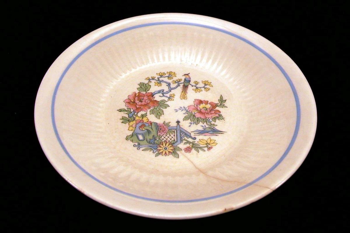 Dyp tallerken med hvit glasur og østen-inspirert dekor i blått, rødt, gult, grønt. Det er sprekk i godset.