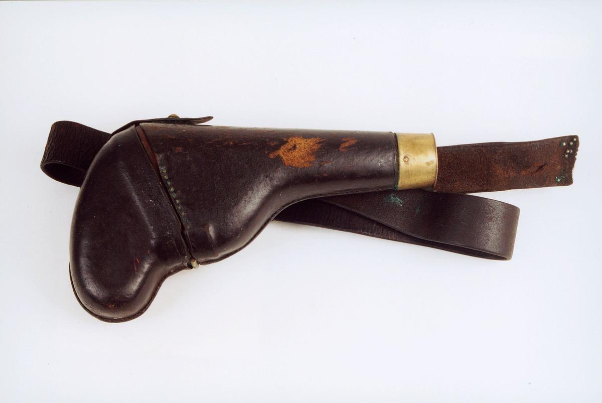 Lærhylster til revolver nr. P0712. Lærovertrukket trefutteral med topp festet med gangjern av messing. Dupsko av messing og bred sort lærrem med messingspenne. ca. 1860
