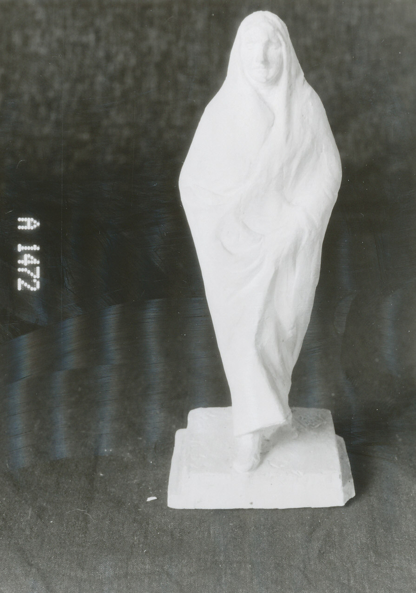 Kvadratisk plint, menneskefigur, gående med venstre fot frem, ansikt litt venstrevendt, fotsidt draperi også over hodet, høyre hånd holder fold