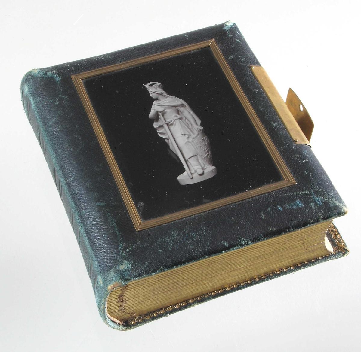 """På forsiden av permen rektanguært  glass, med et   fotografi  under av stående skulptur  mot sort bakgrunn: stående krigerinne med sverd og skjold med dobbeltørn.(antag. t  17,2 x 14,5. Tykkelse ca. 5,5  Innhold ifølge blyantnedtegning: """"   Venner fra Konstantinoplel.  """" I Se liste gjenstandsoppl."""