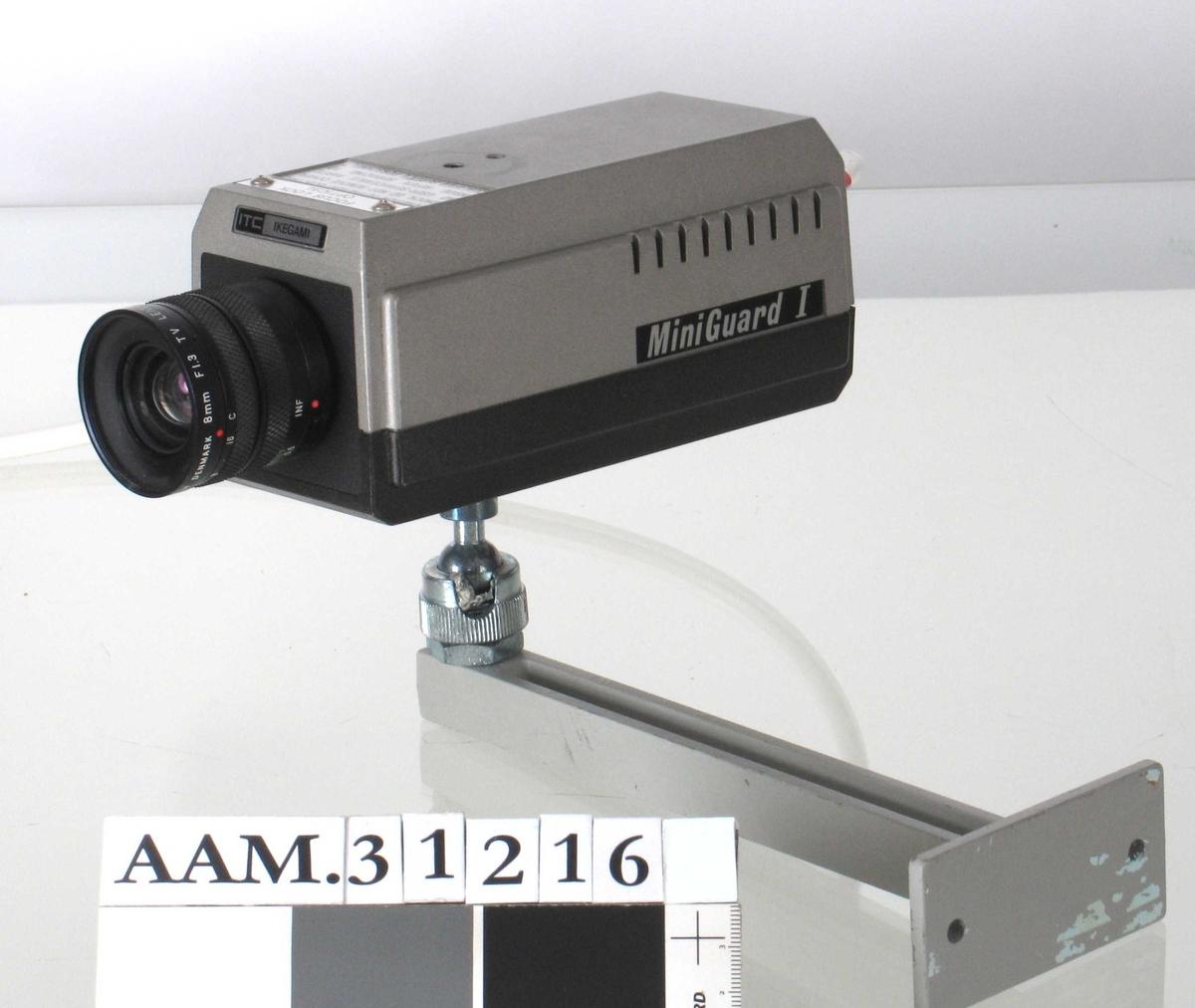 Lite kamera, del av ledning i bakkant. På undersiden festet til arm som har vært skrudd fast i vegg.