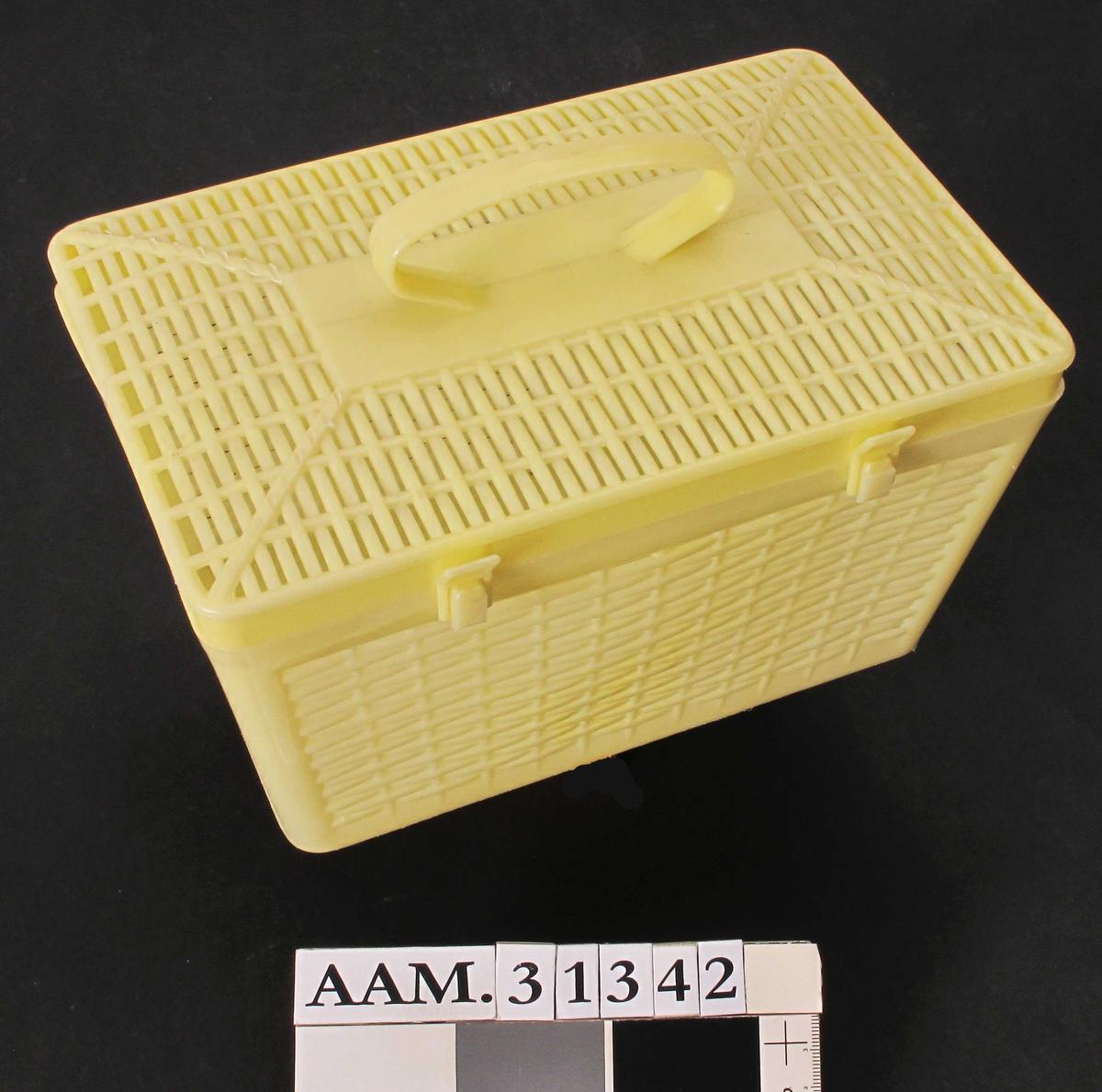 """Lysegul plasteske med hengslet lokk.  Smalner av mot bunnen.  Sidene  er støpt med relieffmønster så de skal se ut som vevd kurv utenpå, og har smale sprekker i mellom """"vevingen"""".  Glatt innvendig.  Lokket er festet med tre hengsler.  Den midterste er noe bredere enn de andre to.  Lokket har også kurvstruktur.  På toppen av lokket sitter det et ovalt bærehåndtak.  Esken lukkes ved help av to tapper som stikker ut fra kanten i lokket.  Tappene passer nedi en knott på selve esken, og låses på plass med en klaff/løkke"""