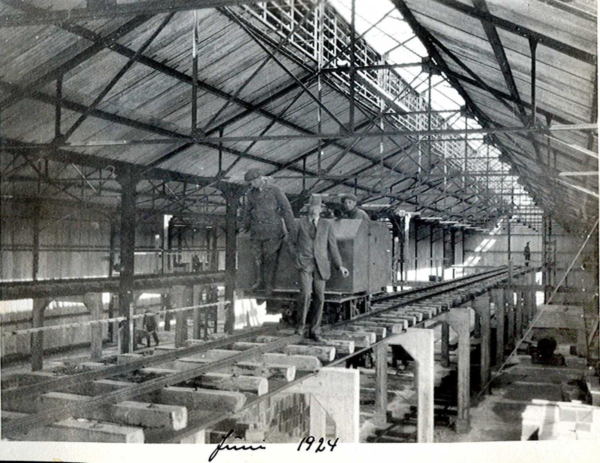 """""""xx/06-1924"""" Nitriden. I en av bygningene for steking av elektrodekull. Her sees bærende konstruksjoner for skinnegang, """"høybane"""", med sviller og dieseldrevet lokomotiv."""