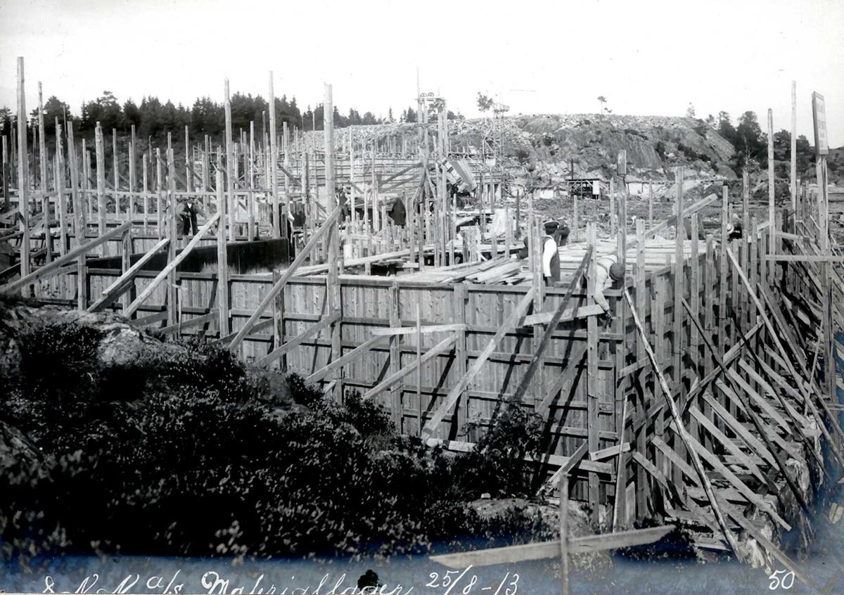 """""""25/08-1913"""" Nitriden. Forskalinger og støping av materiallagerbygningen, som også inneholder verksteder og kontorer. I bakgrunnen planert tomt for svovelsyrefabrikk, som ikke ble noe av."""