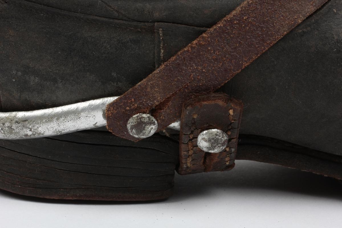 Støvleskaftet er sydd sammen bak, påsydd forsterkning. Inne i skaftet to små lærstropper. Hælstykke og fotstykke sydd til skaftet. Lærsåle. Sporen festet med reim til støvelen, maken til US 444
