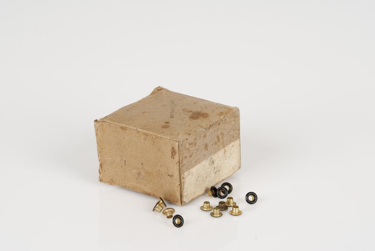 Maljer av metall i en pappeske. Maljene er runde og i fargene sort og gull. Påført tekst på esken.