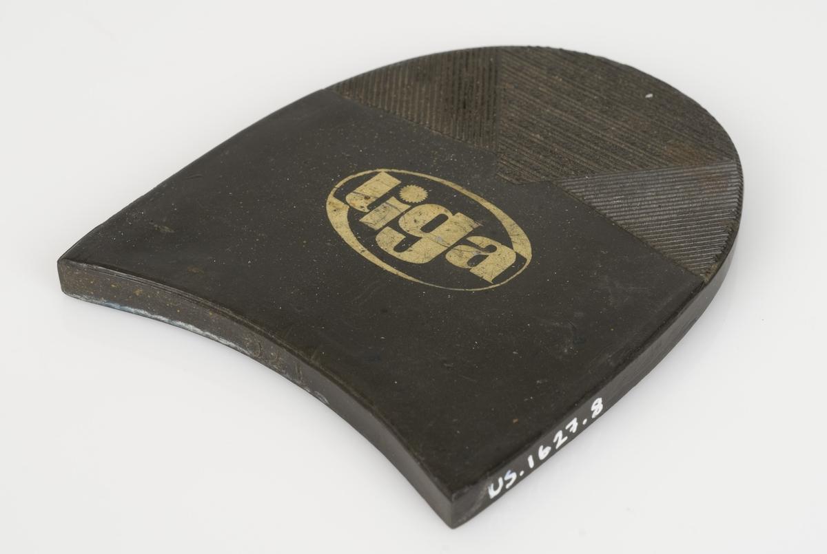 En hælflikk av plast. Fargen på hælflikken er sort. Avtrykksmønster på hælflikken. Påført tekst i gull på hælflikken.