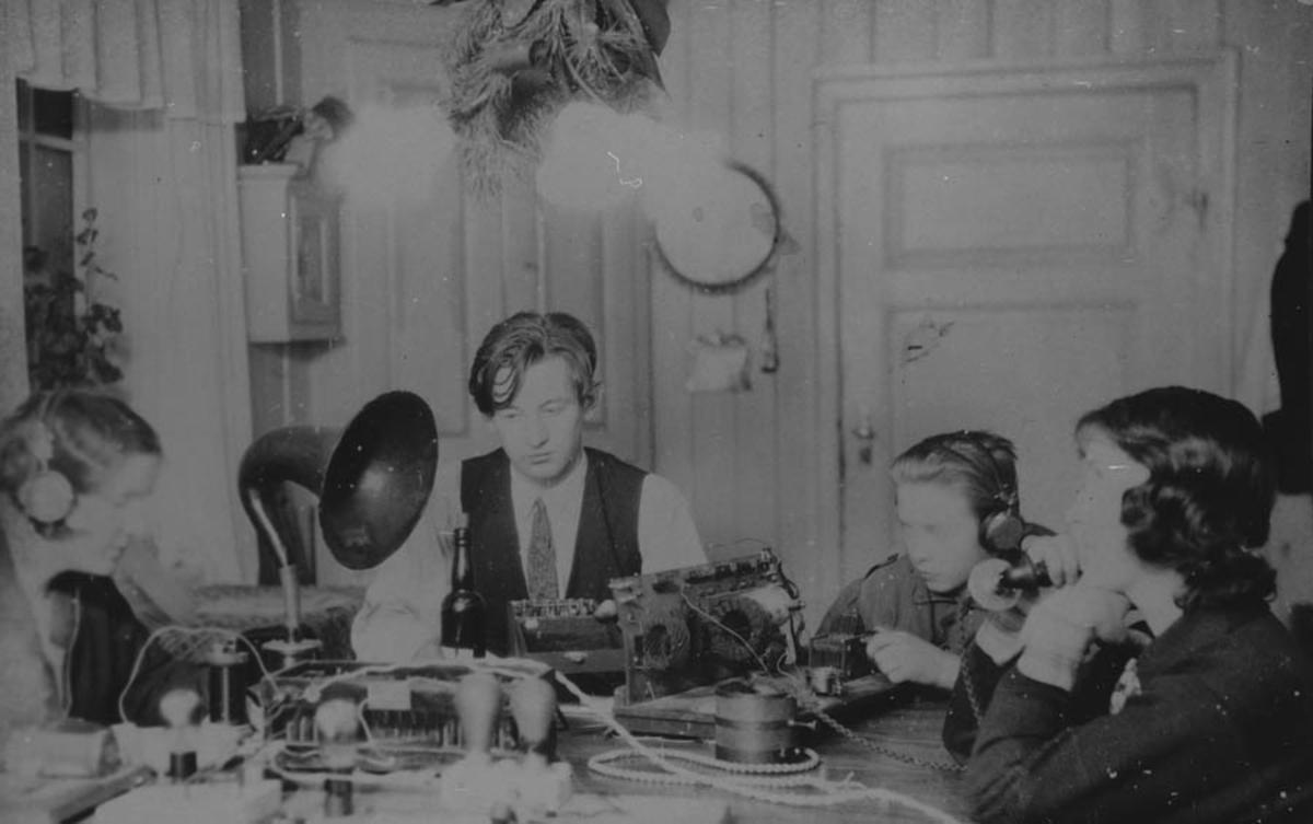 Gruppe rundt et bord med eldre radiomottakerutstyr.