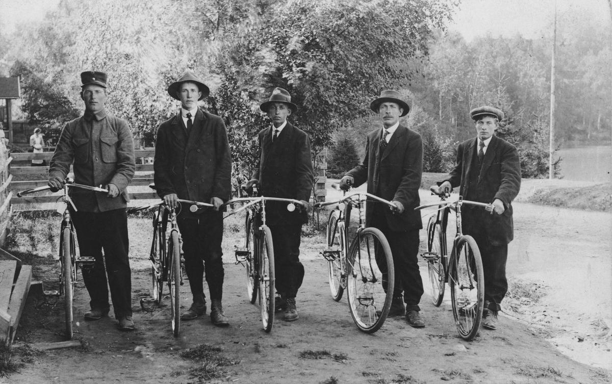 Gruppebilde. Fem menn med sykkel.