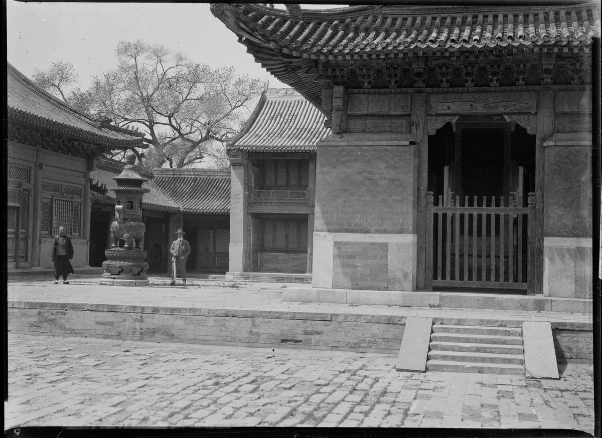 To personer ved en statue. Et stort bygg rundt dem.