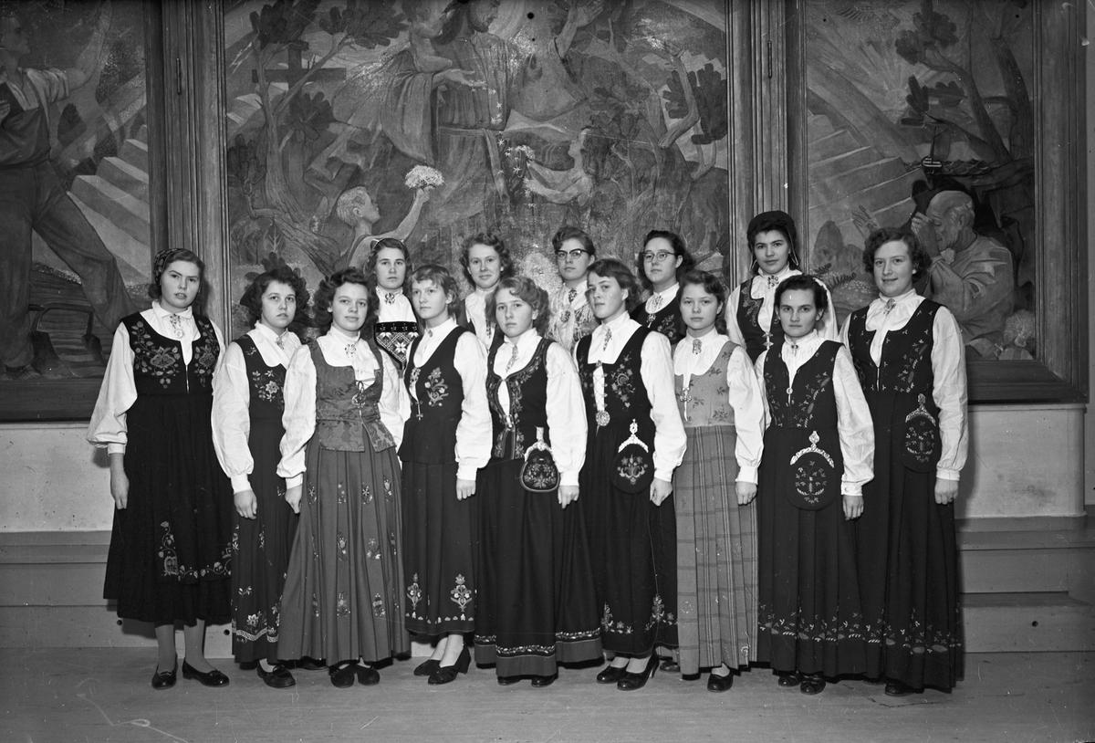 Bjerkely Ungdomsskole. Kvinner i bunad foran veggmaleri.