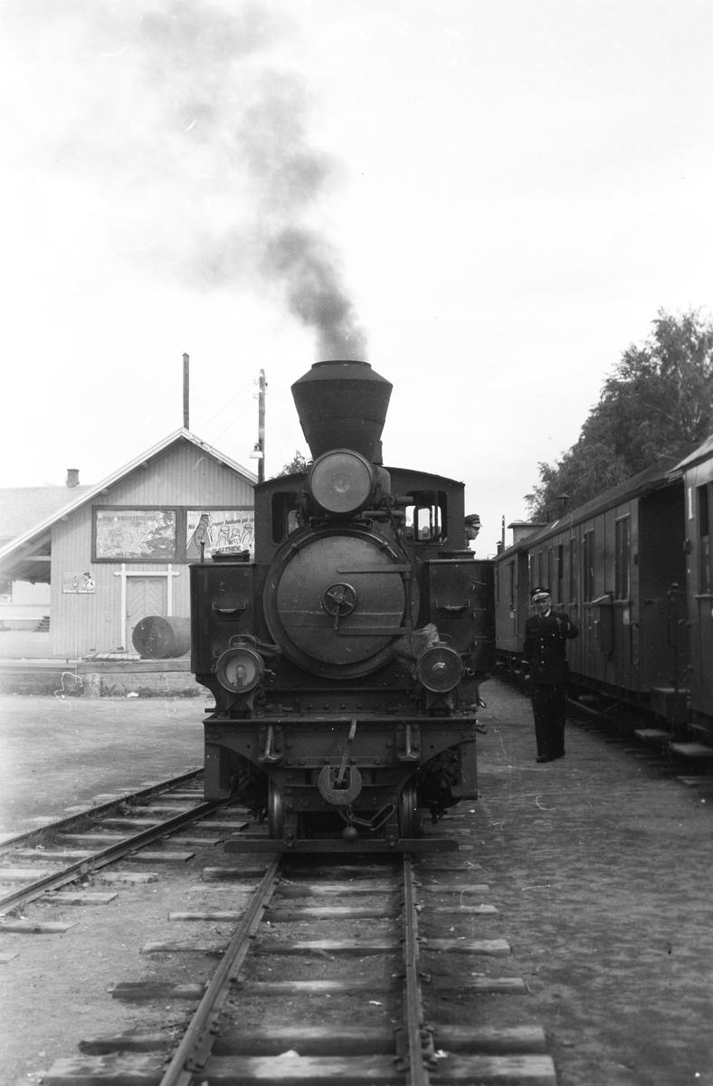 Tog 2051 retning Skulerud skifter på Bjørkelangen stasjon. Godshus Bjørkelangen i bakgrunnen.
