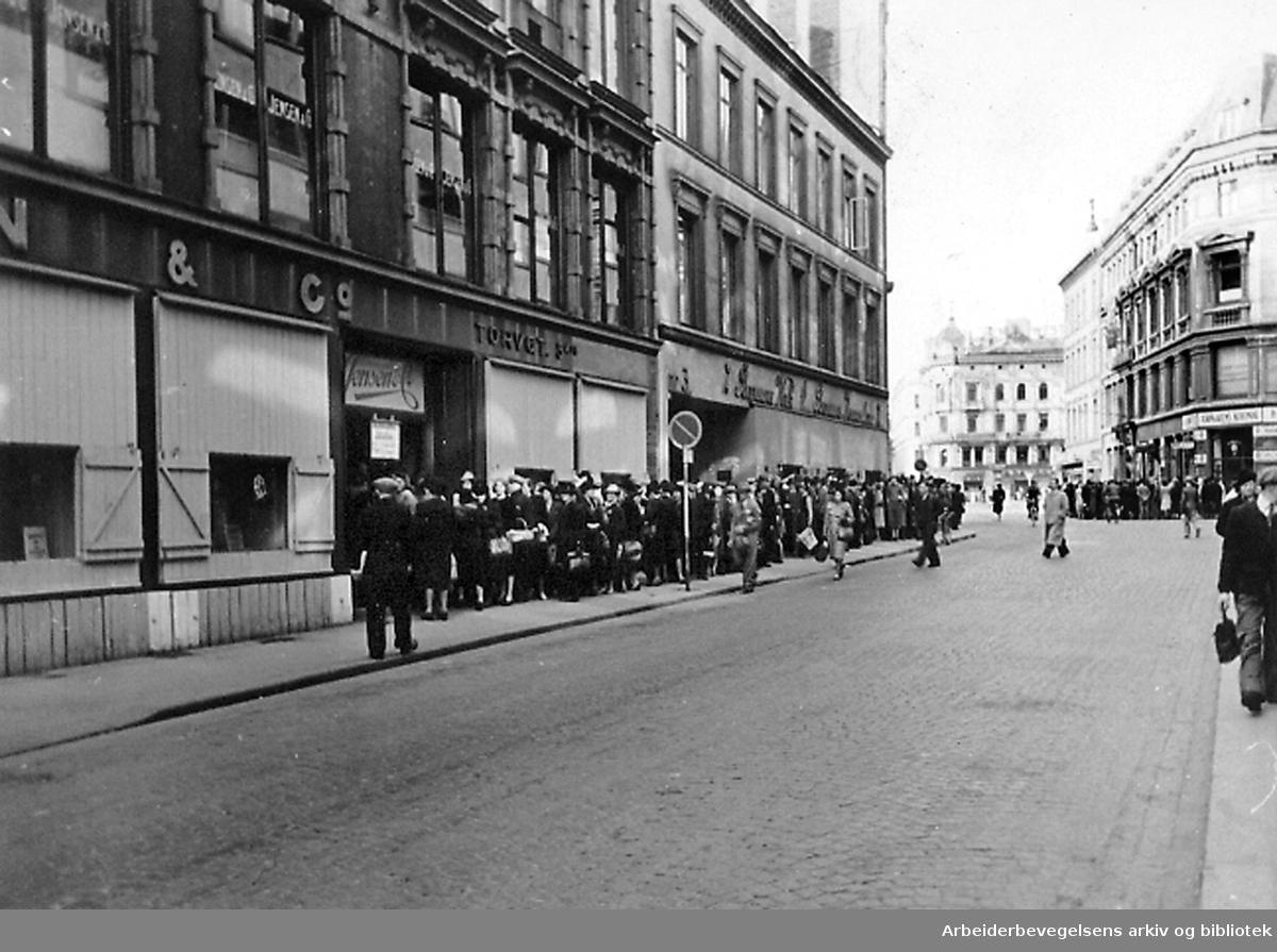 """Stenging av butikker i forbindelse med """"den nasjonale arbeidsinnsats"""" førte til lange køer før stengingen,.1940-45"""