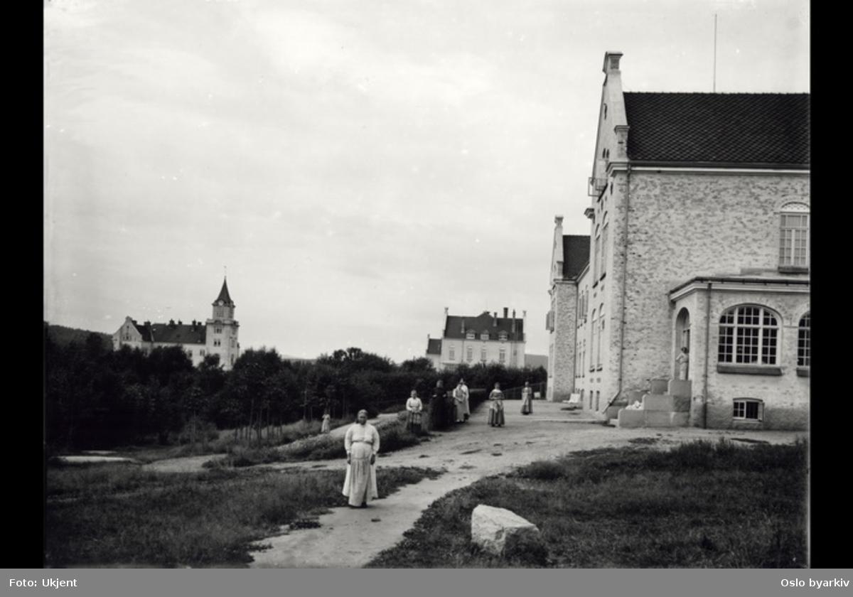 """Bygning """"Slottet"""", flere kvinner ( i lange kjoler) sees ute, bygninger i bakgrunnen."""