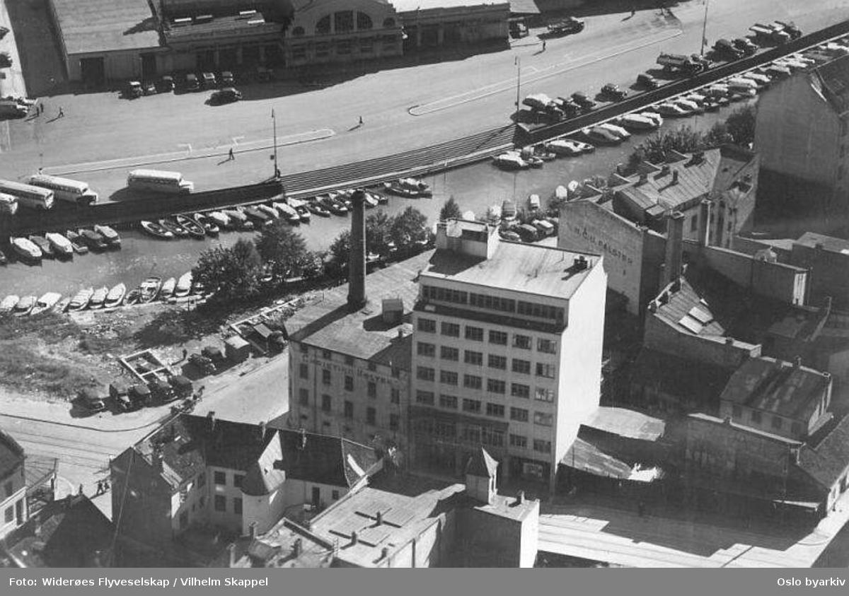 Elvegata (tidl. Bolverksgata), Tomtebrygga (frem til 1972), Vognmannsgata. Tranraffineri, såpe- og lysfabrikk i Elvegata 15. Akerselva. Slaktehuset (Oslo Slaktehus med Kjøtthallen) i bakgrunnen. (Flyfoto)
