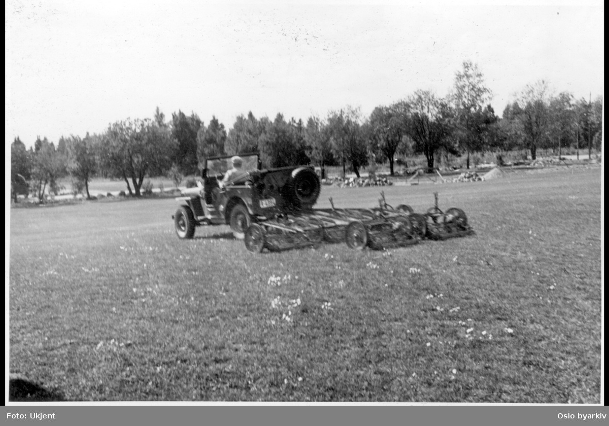 Jeep trekker gressklipper-maskin på sletta.