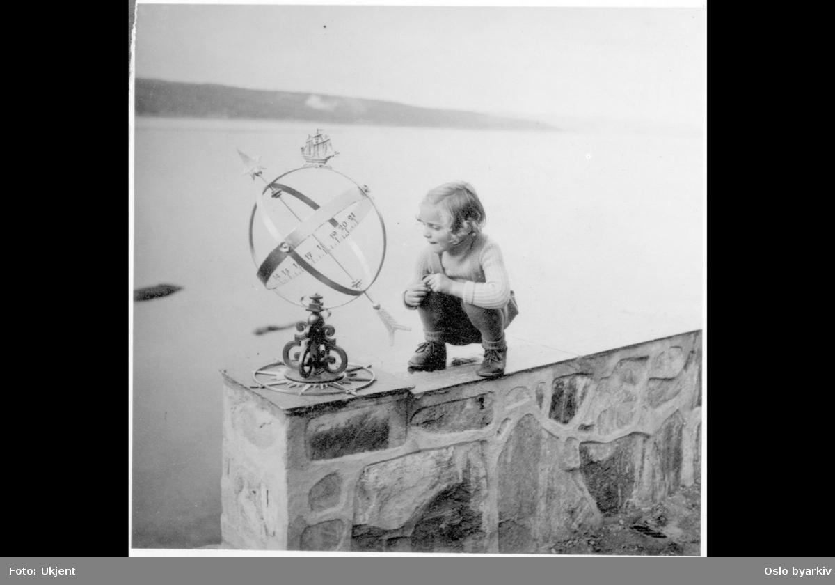 Pike på muren mot sjøen som ser på ett solur. Ingierstrand bad?