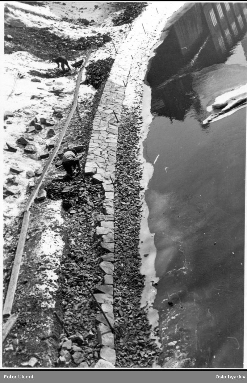 Arbeidere steinlegger Akerselvas bredder en vinterdag. Med spett og rettebord (og plank for trillebår) formes traseen av flat naturstein. Østre elvebredd fra Grünerbrua langs Nedre gate. Vannspeil av Nedre gate 3 (Stolmaker Engebretsens hus).