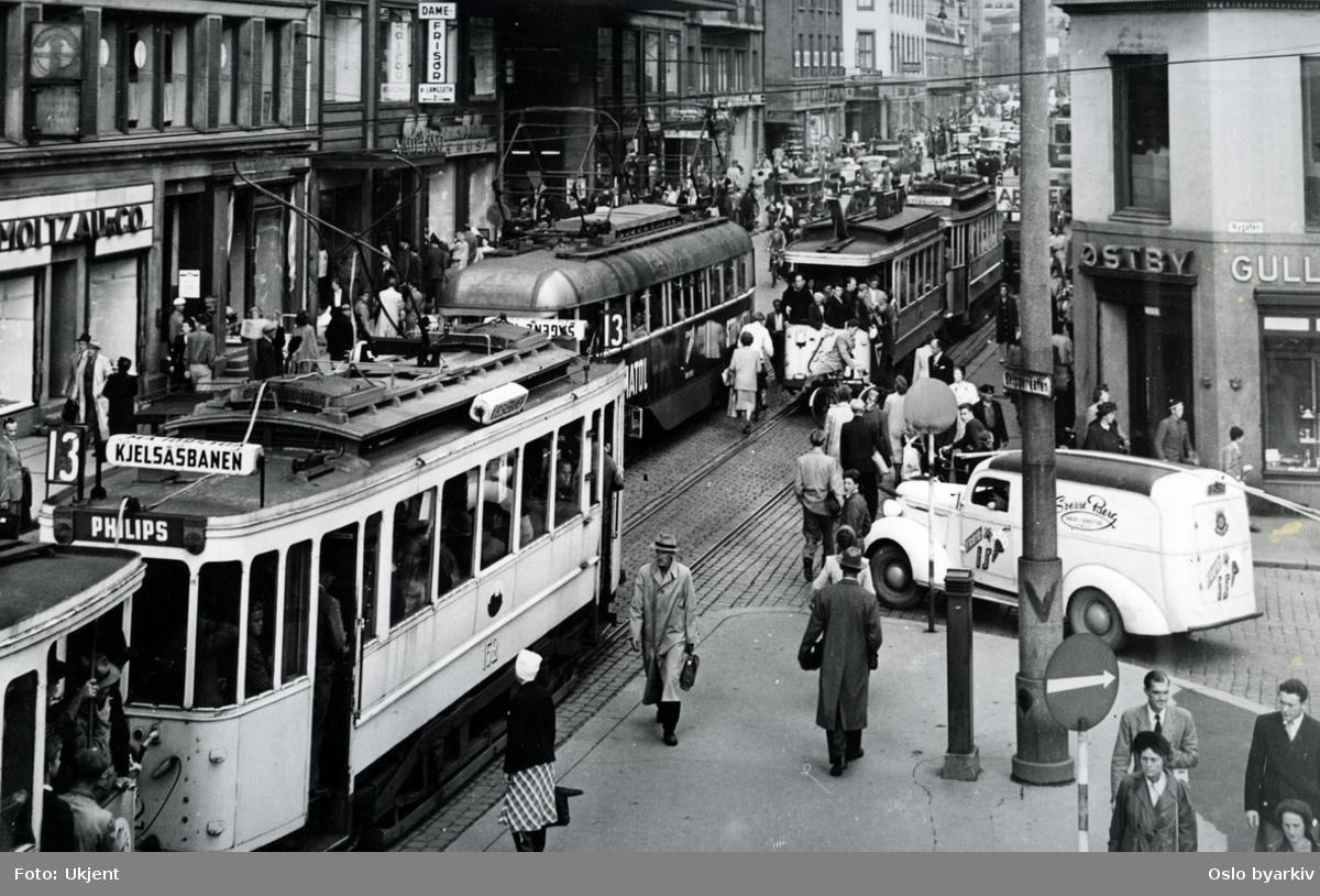 Trafikkmiljø i Storgata ved hjørnet mot Skippergata og Nygata. Sterkt trafikkert gate med trikker, biler og fotgjengere. Gullsmed Martin Østby, Storgata 14. Trikk på linje 13 til Kjelsås (1949-1953) i forgrunnen til venstre. Butikker, butikkskilt.