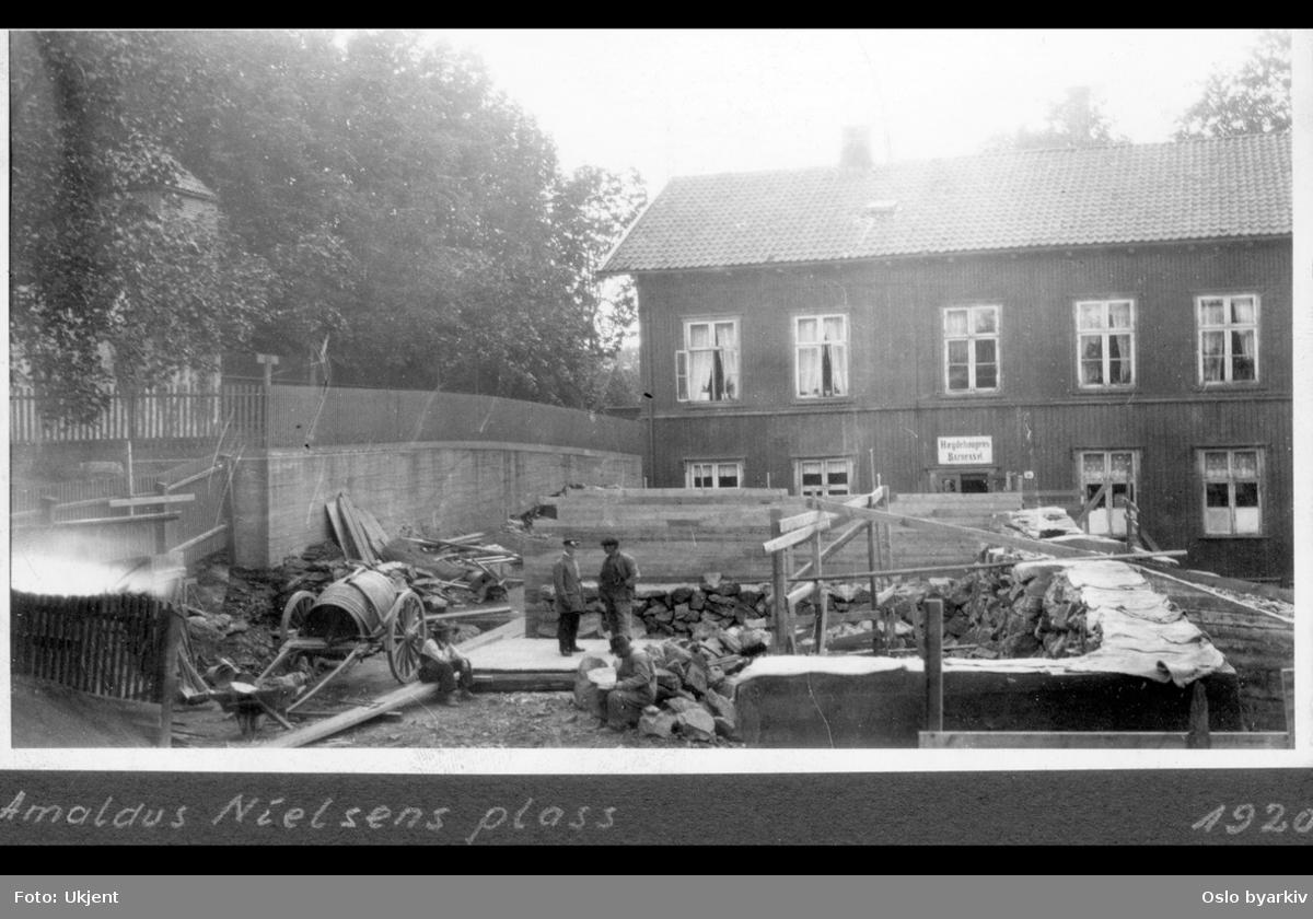 Arbeidere i gang med bygging av den fem meter brede trappen opp til Professor Dahls gate i den østlige enden av plassen ( Professor Dahls plass, Vestkanttorget). I bakgrunnen Langårdsløkken. Trebygningen (fra 1859, skole) merket Hægdehaugens asyl (Grunnlagt som Hegdehaugens Asyl 1872) i Professor Dahls gate 36 huser Hegdehaugen daghjem siden 1886.