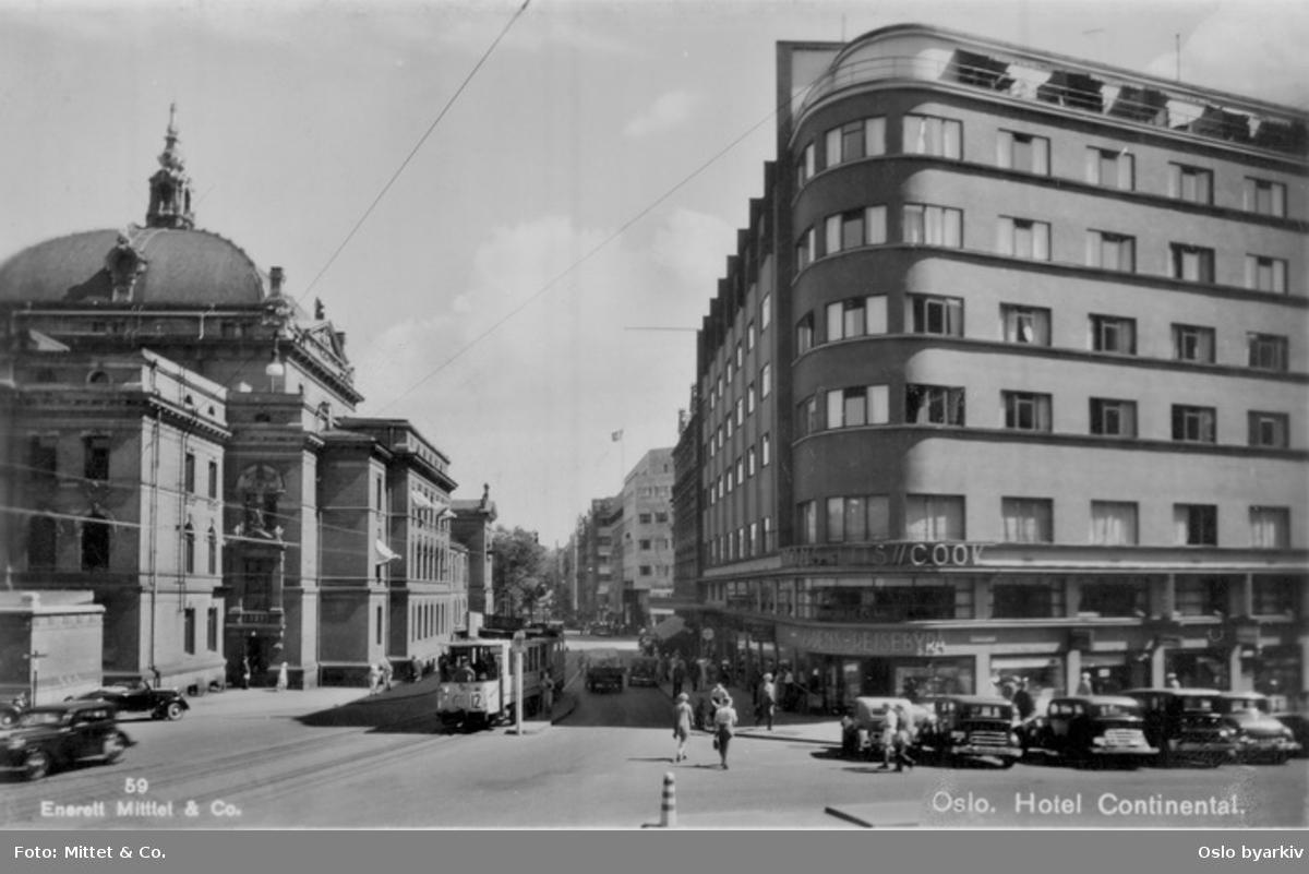 Stortingsgata mellom Nationaltheatret og Hotel Continental (med Wagons-Lits/Cook reisebyrå på hjørnet). Roald Amundsens gate (dagens Olav Vs gate) til høyre. Trikk, biler, spaserende. Postkort 59.