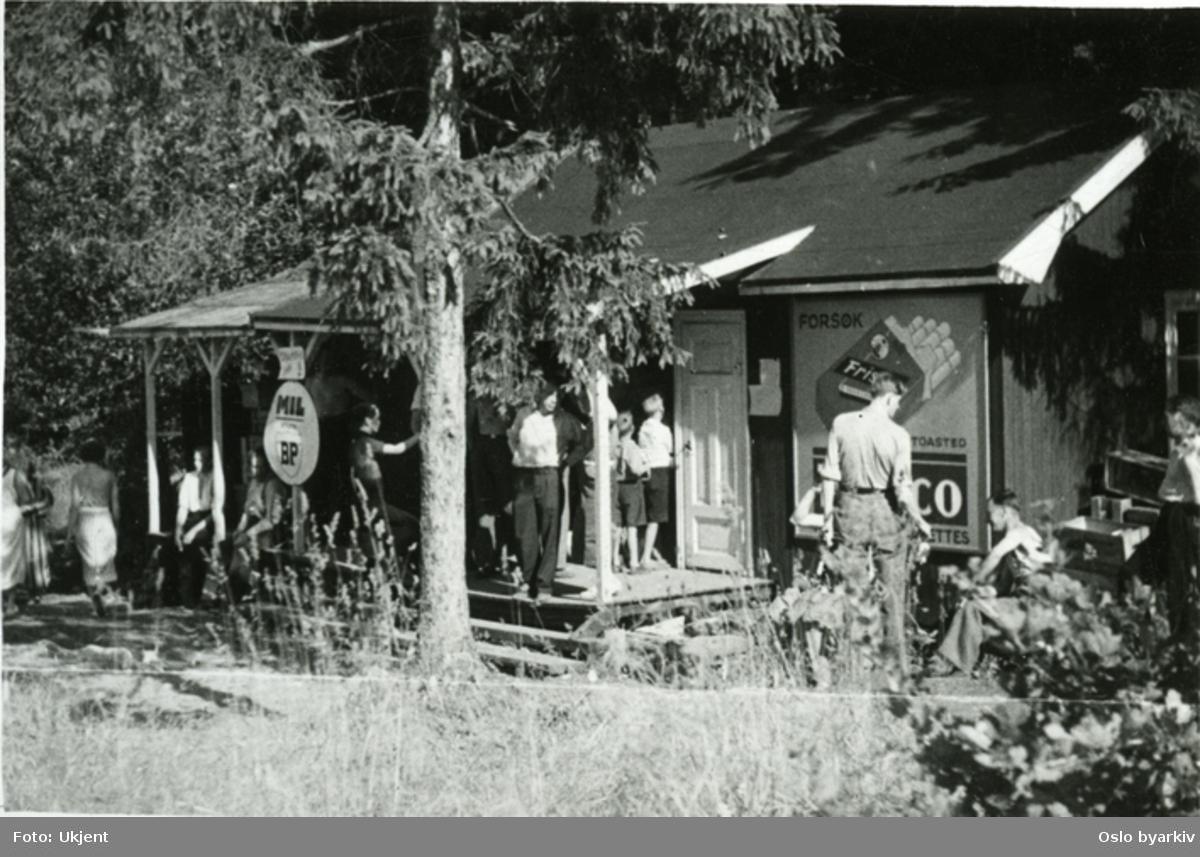 Butikken på Vestsiden av Nordre Langåra mot Langårssund, bygget første gang i 1927.Tilbud på bensin og olje (MIL-BP). Barn og voksne i kø foran utsalgs luka. Reklameplakat for Frisko sigaretter.
