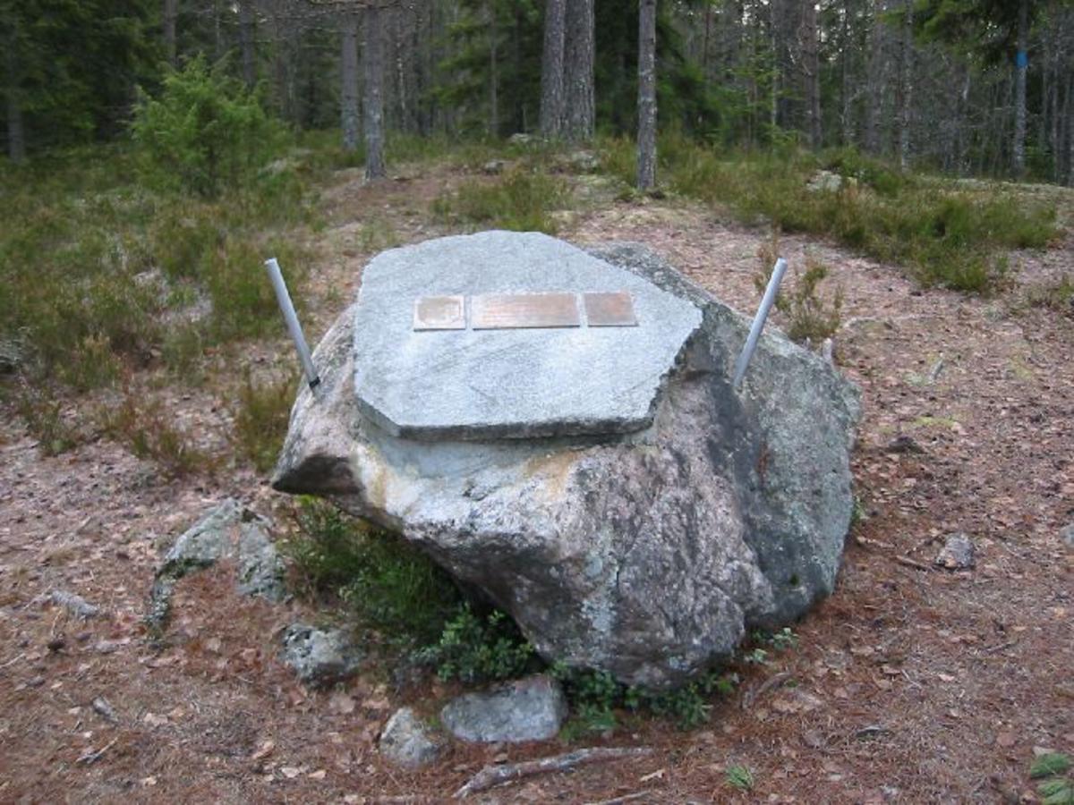 To skjold og en plate festet til stor stein.