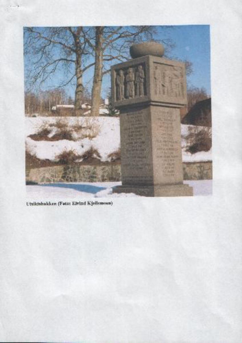 Dekorert firkantet steinbauta med inskripsjoner på steinlagt og beplantet parkområde.