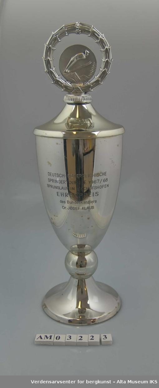 Form: Pokal med kuleformet vulst og lokk med lokkgrep i form av laurbærkrans rundt skihopper.