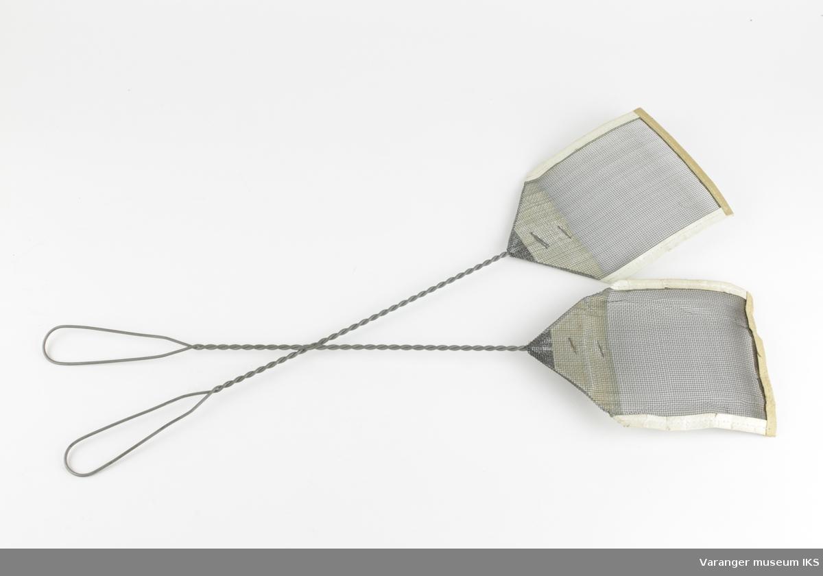 Et par identiske fluesmekkere i metall. Skaft av tvunnet ståltråd. Smekkeflaten er av finere netting. Ytterkanten av smekkeflaten er omsluttet av lær eller kunstlær.