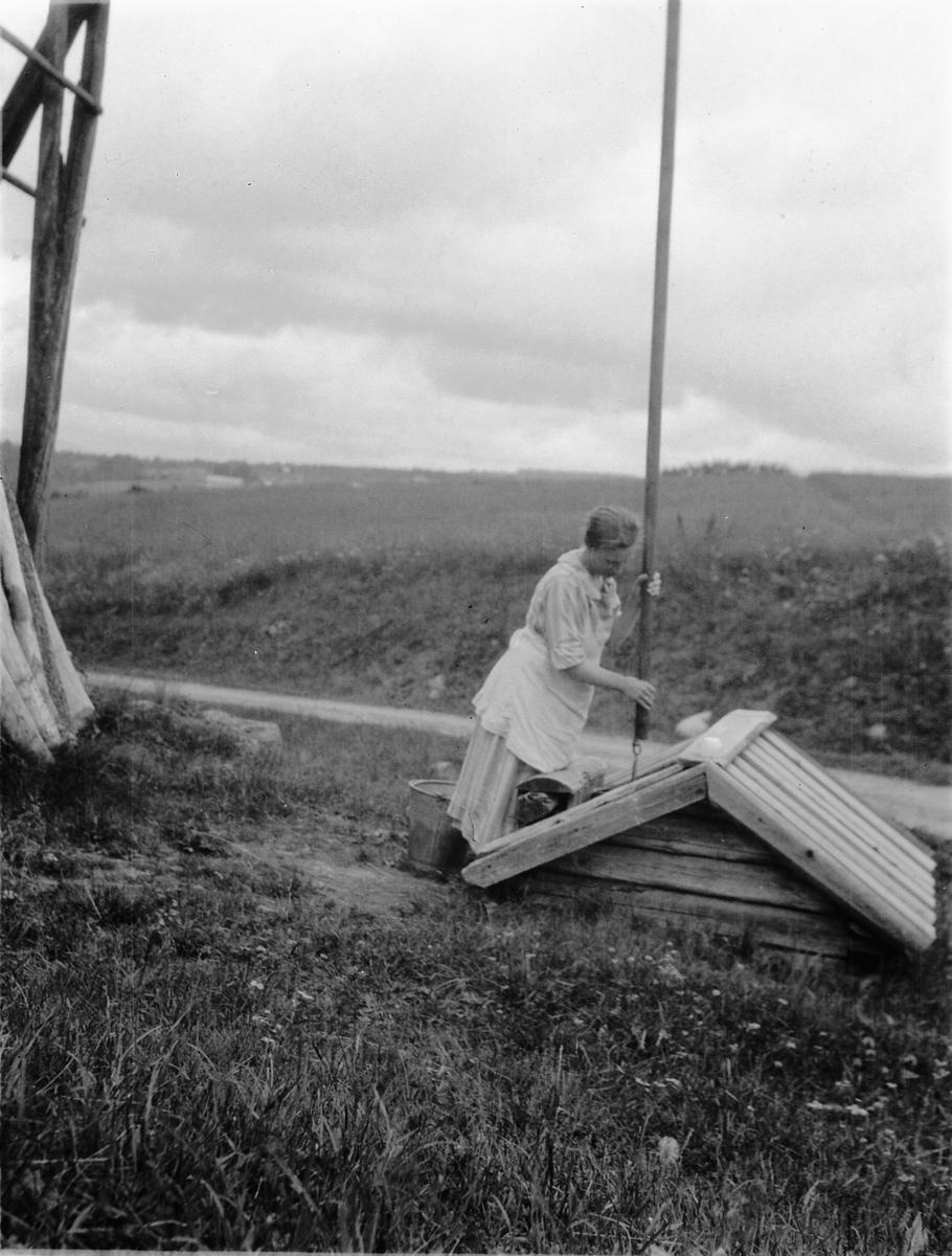 Ukjent kvinne henter vann ved en vannpost, brønn.