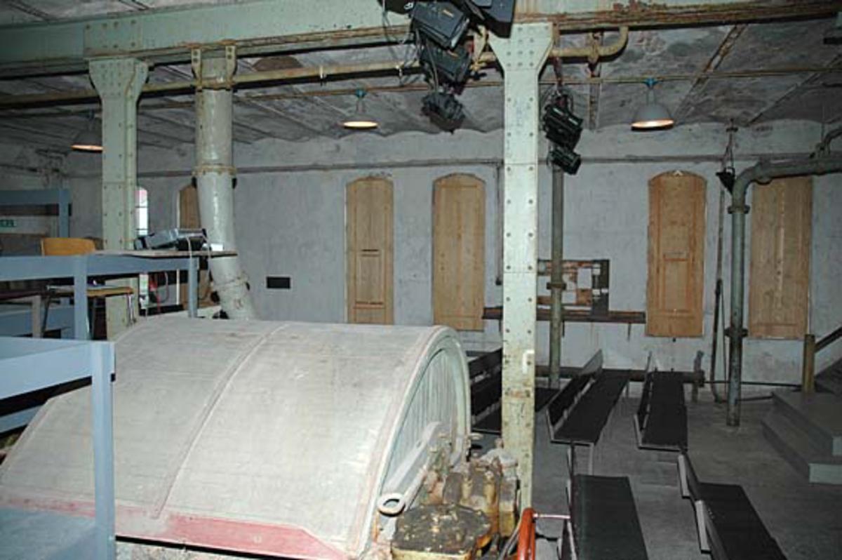 Fra hollenderisalen ved Klevfos Cellulose- og Papirfabrik i Løten i Hedmark.  I forgrunnen ser vi det gråmalte tredelselet over hollenderkaret, der råstoffene som skulle inngå i papirmassen ble blandet og malt sammen.  Ellers viser fotografiet hvordan rommet var bygd, med pussete og kvitkalkete teglsteinsvegger og et tak som ble båret av klinknaglete jernsøyler og jernskinner.  Disse bar et etasjeskille som var bygd som kappehvelv - slake teglsteinsbuer mellom jernskinner.  Hollenderisalen har, etter at fabrikken og dens nærmeste omgivelser ble industrimuseum, vært brukt som teaterlokale for forestillingen «Arbesdaer».  Dette er bakgrunnen for at det er satt inn benkerader i lokalet, og for at de høye støpejernsvinduene er forblendet med trelemmer.  Ved å fjerne mesteparten av lysinnsiget får man full nytte av teaterlyskastrene, som skimtes oppunder taket. Ådalsbruk.