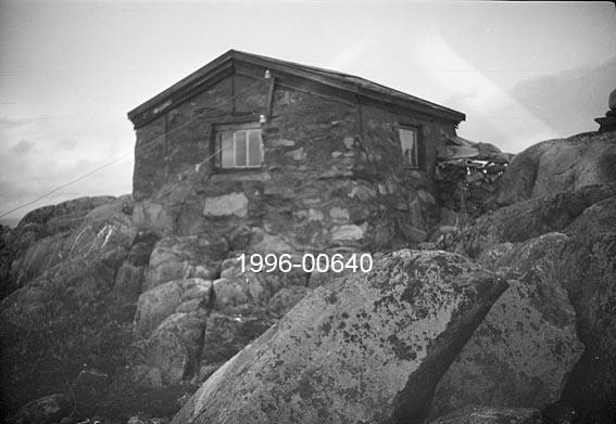 Hytta på Byringen skogbrannvaktstasjon i Ytre Rendalen.  Dette fotografiet viser (i motsetning til SJF. 1996-00639 og SJF. 1996-00641) en murt steinbygning med saltak.  Hytta ligger på berggrunn i et vegetasjonsfattig landskap.   Byringen ligger øst for Storsjøen, 1 031 meter over havet.  Brannvaktstasjonen her ble bygd av skogeier Simon Sjølie (f . 1865) på Nedre Sjøli i 1904, men seinere overtatt av Ytre Rendal Skogbrannkasse.   Opptaket er dessverre noe uskarpt.