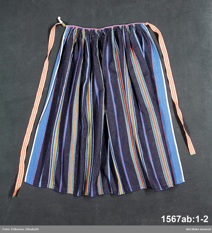 a. Förkläde av halvylle,  varp av oblekt lingarn, inslag i rips av tunt ullgarn, mörkblå botten med grupperade ränder i  ljusare blått, rött och grönt ullgarn samt vitt lingarn. Upptill rynkat mot smal midjekant av blå/rödmelerat halvylletyg. I ändarna fastsydda mässingshakar med påhakade knytband litt b:1-2,  av  3 cm breda  fabriksvävda röda ylleband med  rutmönster i vitt lingarn. Bandändarna kantade med grönt sidenband.  /Berit Eldvik 2012-04-27