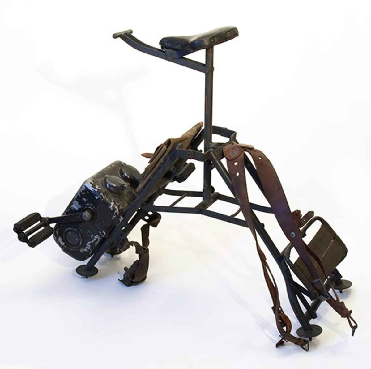 Tysk generatorsykkel fra 2. verdenskrig. Stativ med sete og pedaldrevet generator. Veske over generatoren. Syklen er sammenleggbar og har bæreremmer for transport som ryggsekk.