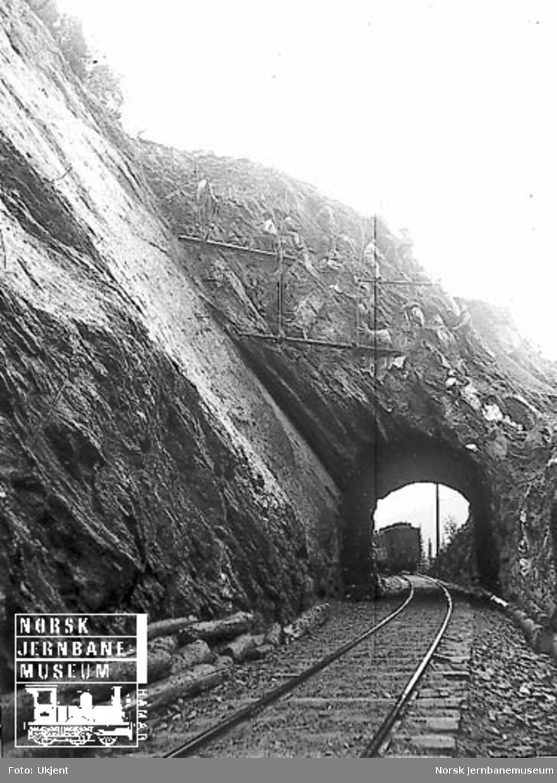 Ni menn utfører fjellsikring ved en kort tunnel, trolig på Flekkefjordbanen : personvogn på motsatt side av tunnelen