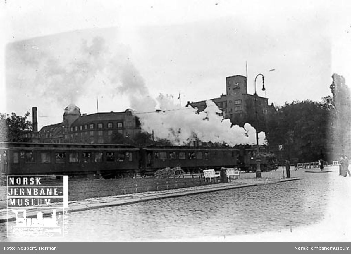 Damplokomotiv av type 23b foran et persontog på vei over Rådhusplassen