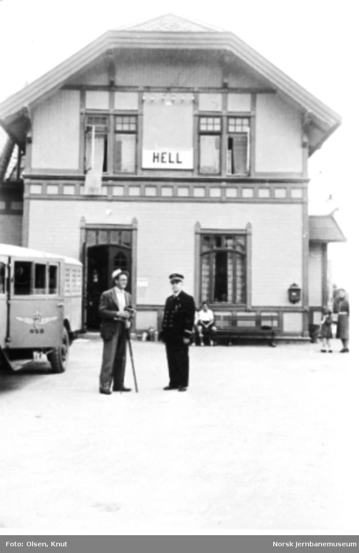 Hell stasjonsbygning, gavlpartiet; en av Selburutens kombinerte biler står på plattformen sammen med stasjonsmesteren og en fotograf