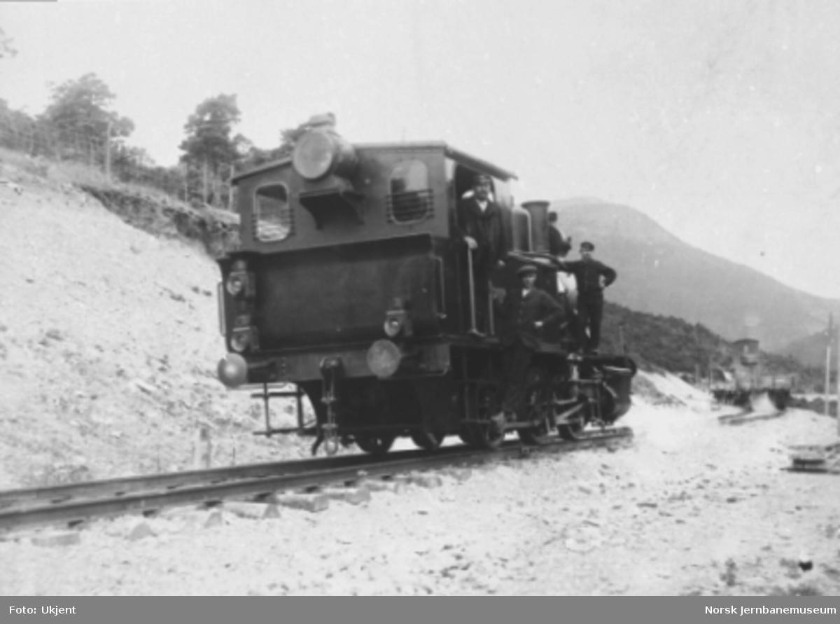 Damplokomotiv type 25a med tre mann på lokomotivet under grusing nord for Otta