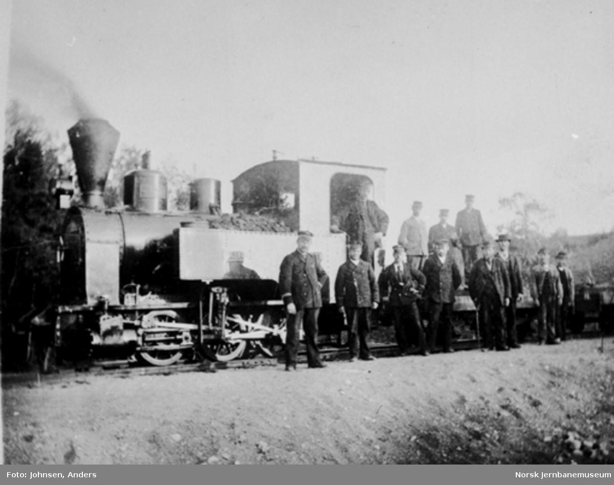 "Lokomotiv nr. 1 ""Urskog"" med grusvogner og personalet oppstilt for fotografering"