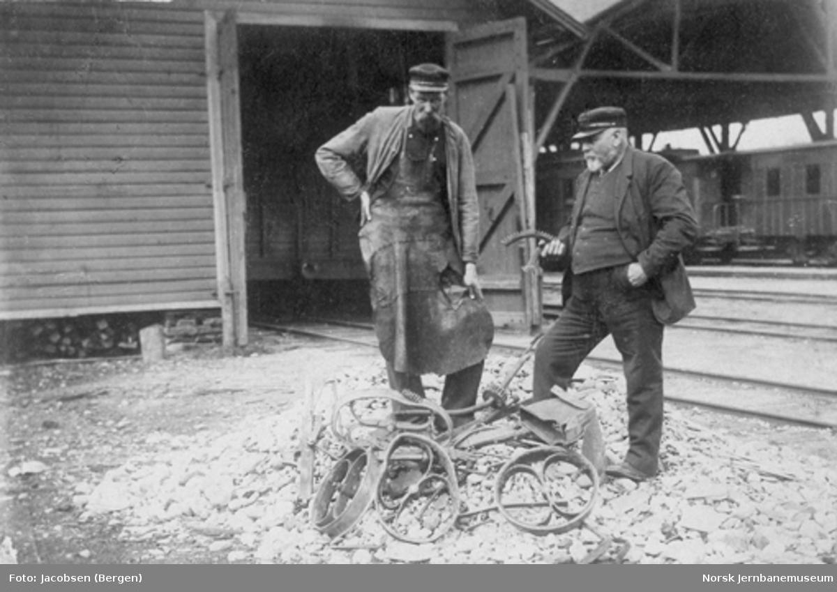 To mann inspiserer restene av en påkjørt håndtralle
