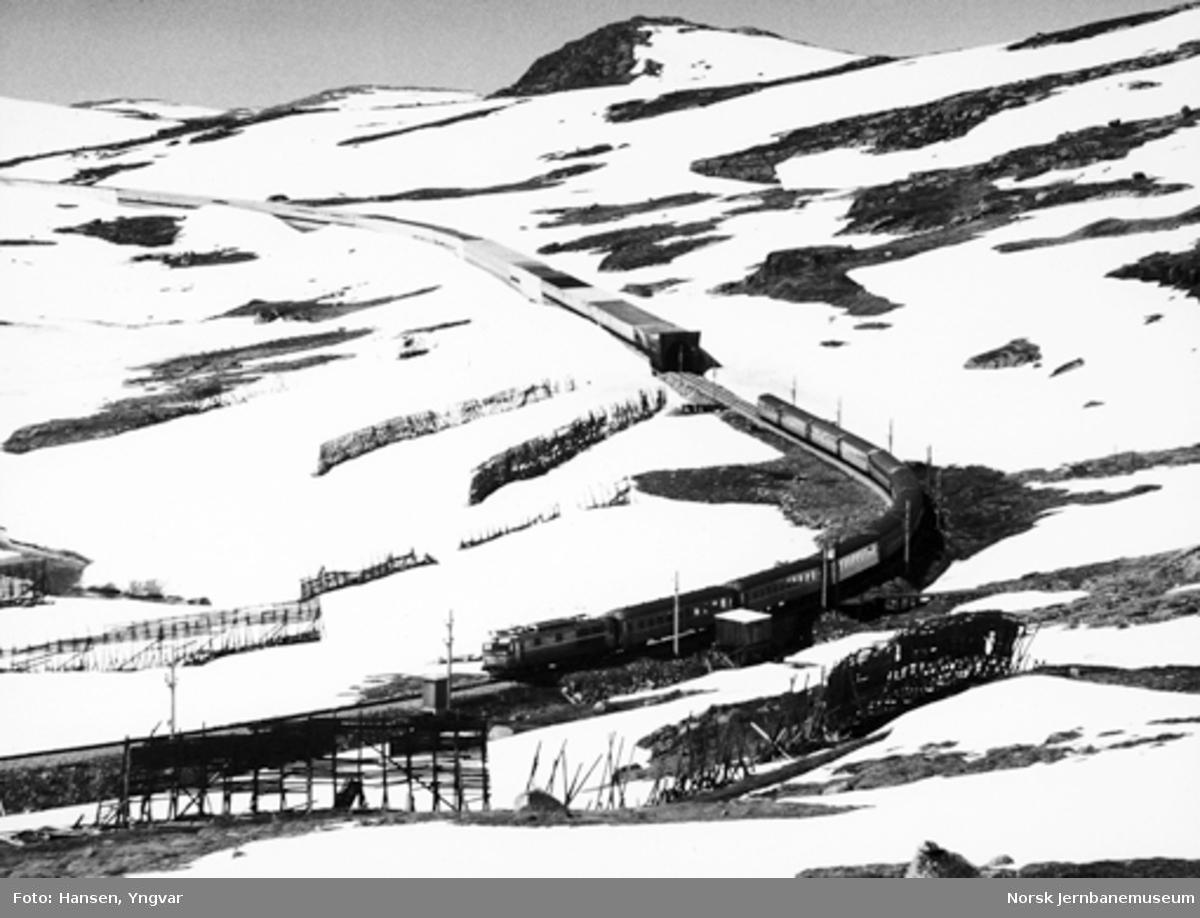 Snøskjermer ved Sandå med snøoverbygg i bakgrunnen og østgående dagtog