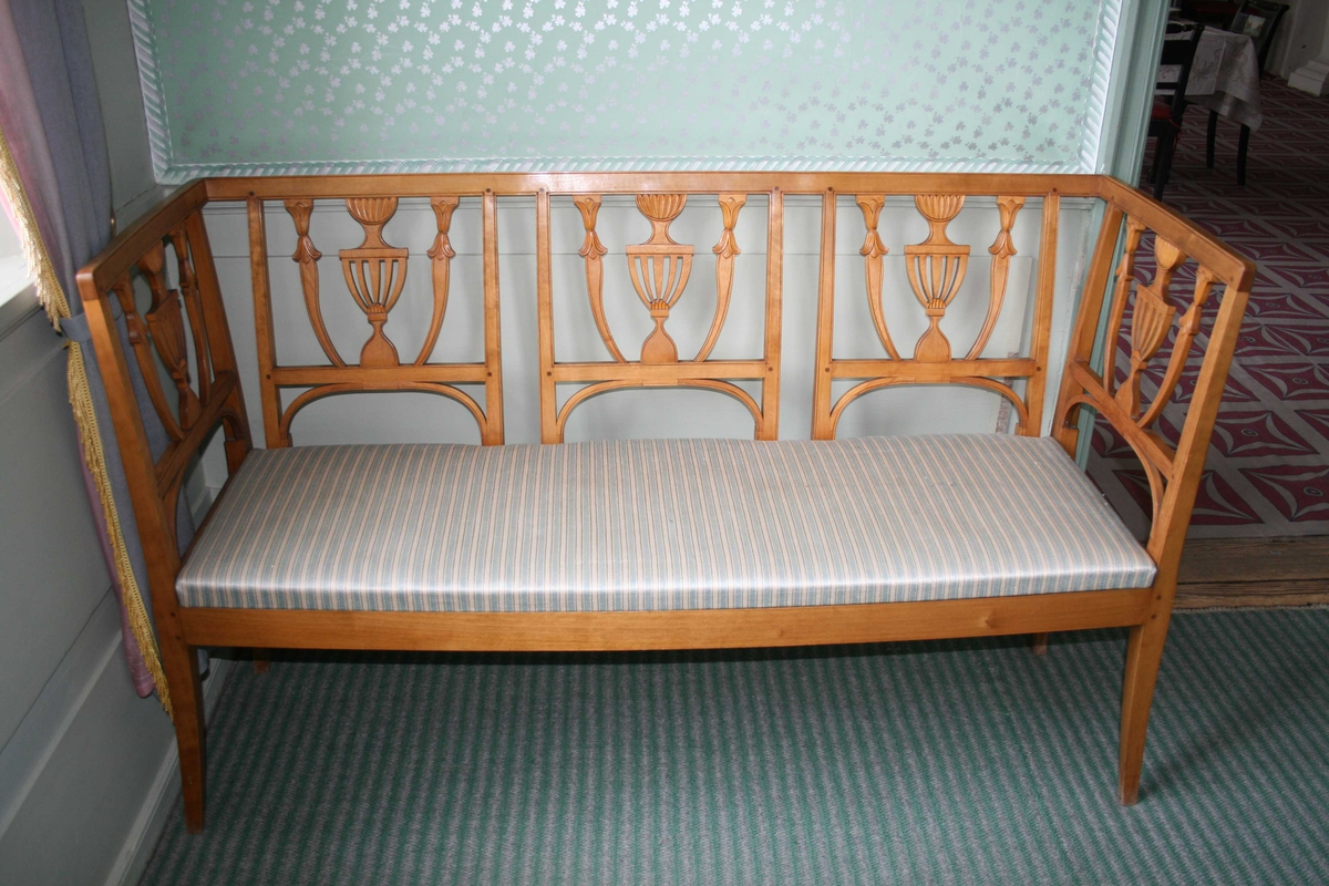 3-sete bjerkesofa i empirestil med ryggbrikke utformet som en urne. Løst sete med stripete trekk, lys blått og lys grått like striper med en mørkere grå tråd innimellom, håndvevet.