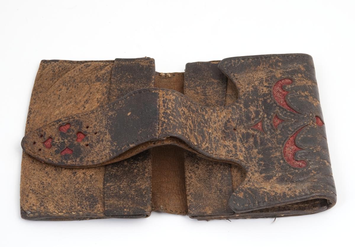 Rektangulær. Brettes sammen og lukkes med reim som festes i hempe på baksiden. Tre lommer inni. Dekor av mønster som er skåret ut i skinnet og foret med rødt tekstil.