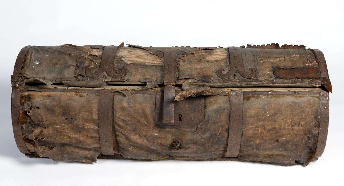 Sylinderformet kiste, med lokk, hanker på kortendene. Kiste av tre trukket med lær. Jernbeslag