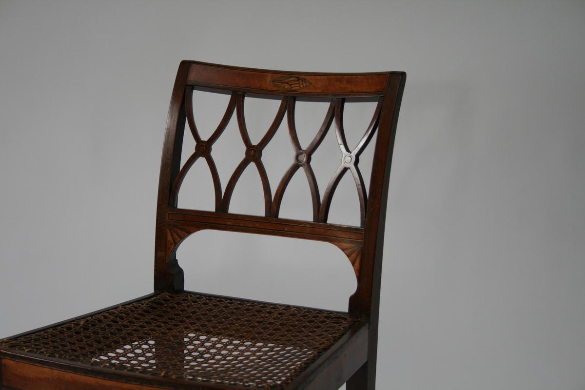 En av 4 mahogny stoler med intarsia; skjell dekor og vifte form. Ryggbrikke skåret ut i fire x-er med en runding i midten. Rotting sete.