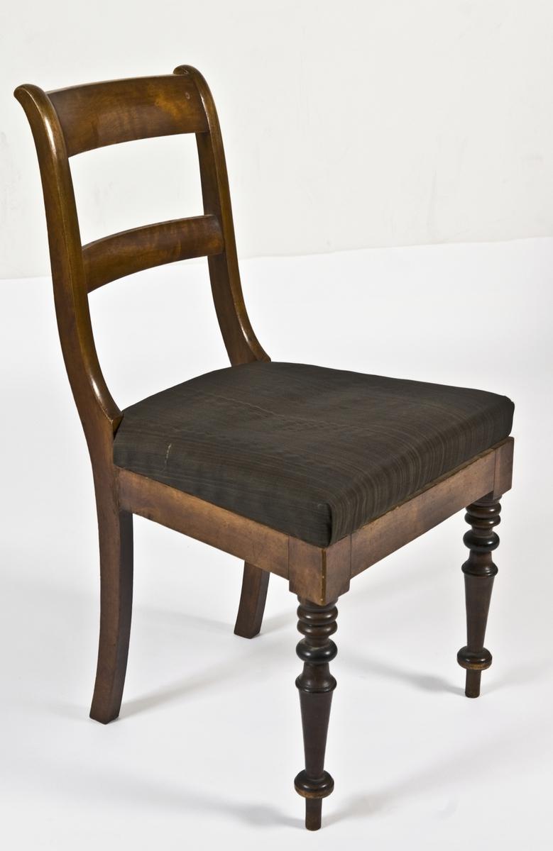 Stol med løst sete trukket med brunsvart tekstiltrekk.