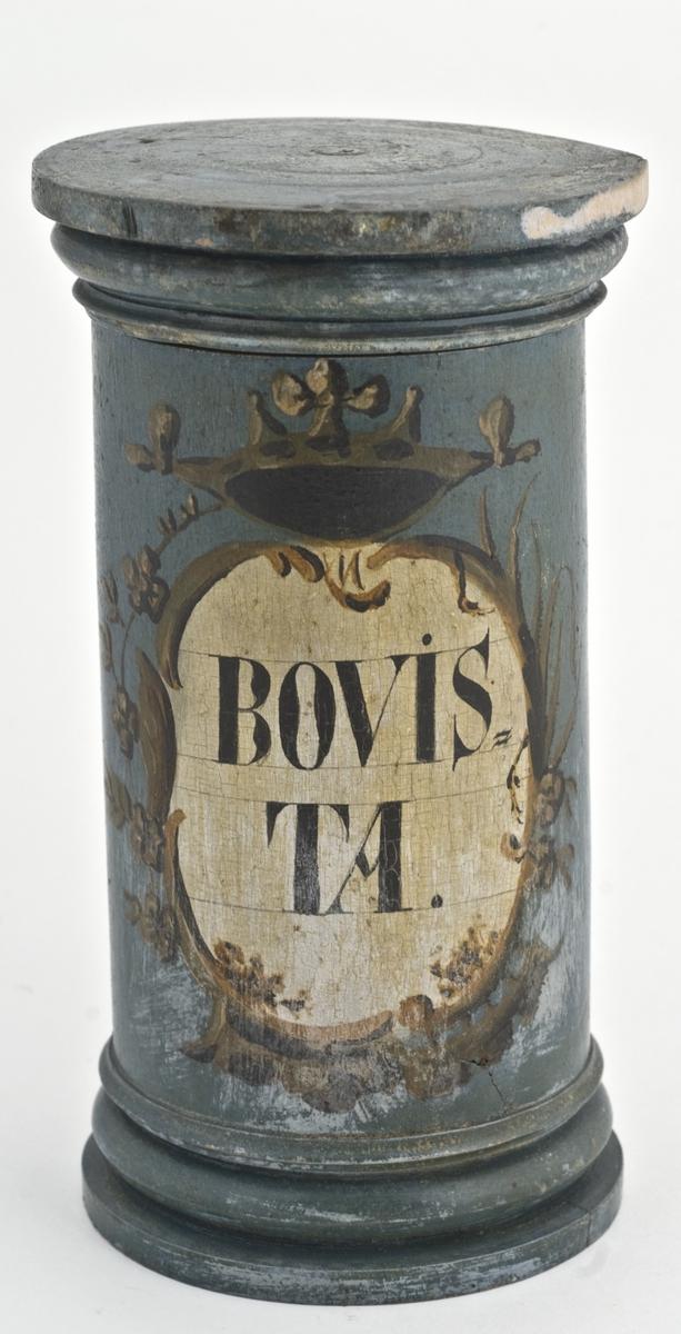 Standkar av tre med lokk. Påmalt oval hvit etikett med krone, blomsterbord, sort skrift og brun kant.