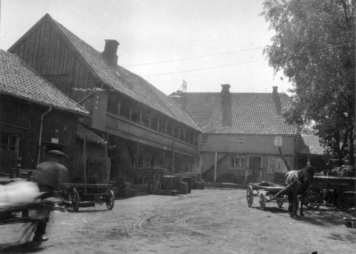 Moss, Østfold. Bygninger ved gårdsplass med kasser og hestekjøretøy.