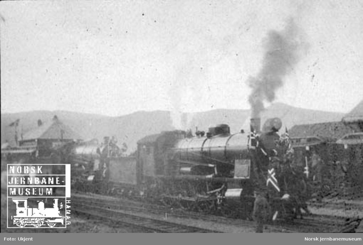 To pyntede damplokomotiver foran persontog på Dombås stasjon; trolig Dovrebanens åpningstog